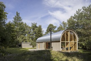 Sited in a small forest clearing near the Kattegat seashore in Denmark, Vibo Tværveh is a contemporary take on traditional Danish cabin and barn architecture. The tube-shaped structure is cladded in pine and topped with rolled steel plates.
