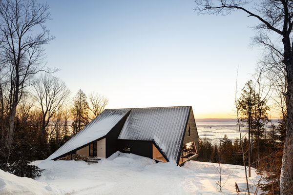 While the cabin was built for year-round use, its location in the village of Petite-Rivière-Saint-François in Québec, Canada, makes for a cozy winter retreat while skiing at nearby slopes.