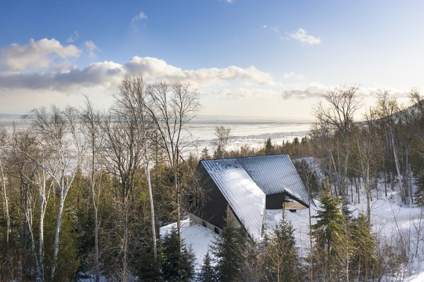 """Cabin A by Bourgeois / Lechasseur architectes is perched on the mountainside overlooking the Saint Lawrence River in Québec, Canada. The """"A"""" in the name references the nautical alphabet of the International Code of Signals (ICS), while the home's angular form was derived from the maritime Alfa signal flag and the shape of a ship's sail facing the wind."""