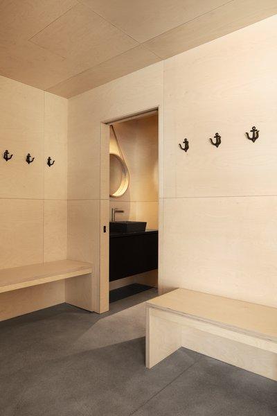 A small bathroom is tucked away near the mudroom, hidden behind a pocket door.