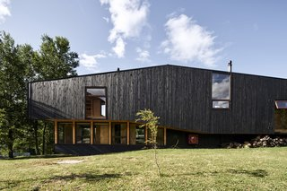 The black-stained wood that clads the south faade contrasts with the glass on the north façade and blends with the color of the tree trunks that pepper the natural landscape.