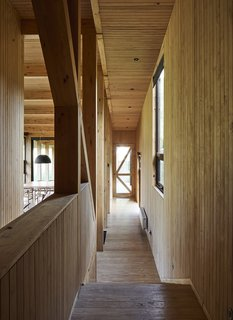 The long, narrow corridor that accesses each of the rooms steps down, marking the transition from the upper-level master bedroom to the public areas, which are located on the house's lower level.