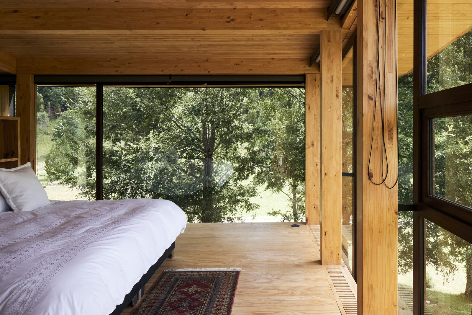 Bedroom, Bed, Medium Hardwood Floor, and Track Lighting The glass walls in the master bedroom allow the treetops to act as a natural curtain, and create the feeling of sleeping in a tree house.  Renovations from A Cantilevered Home in Southern Chile Takes Design Cues From Lake, Trees, and Sky