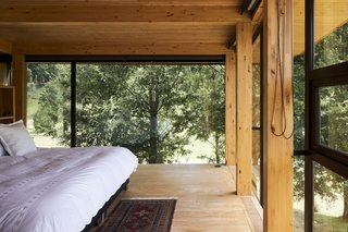 The glass walls in the master bedroom allow the treetops to act as a natural curtain, and create the feeling of sleeping in a tree house.