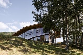 The architects nestled the home into a fold in the topography so that the western facade grips the land, and the eastern facade cantilevers over a small slope.