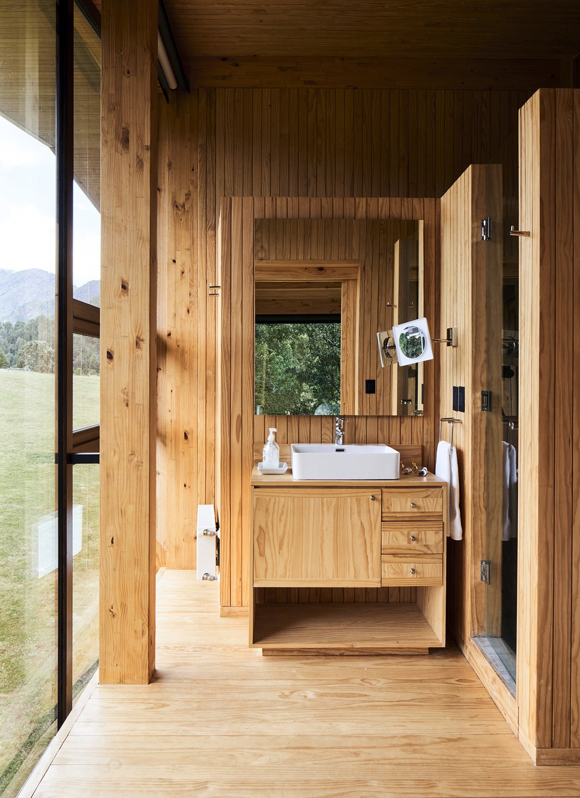 Bath, Wood, Medium Hardwood, Vessel, and Enclosed The raw pine that wraps around the vanity, walls, flooring and ceiling in the bath lends texture and warmth.  Bath Enclosed Medium Hardwood Photos from A Cantilevered Home in Southern Chile Takes Design Cues From Lake, Trees, and Sky