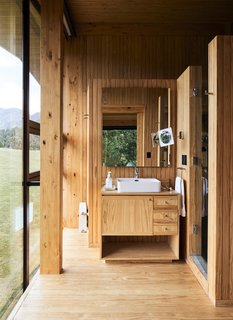 The raw pine that wraps around the vanity, walls, flooring and ceiling in the bath lends texture and warmth.