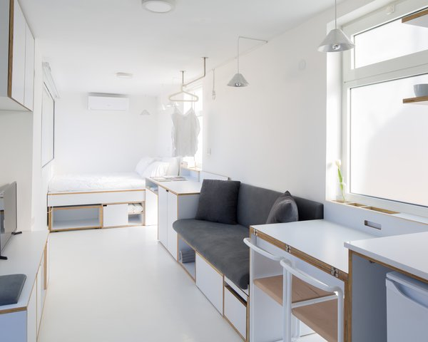 A view from the kitchen shows the built-in storage wrapping around the flat's perimeter. Translucent window panels allow natural an abundance of natural light into the space while providing privacy.