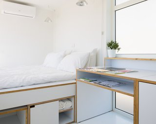 Storage and electrical plugs are offered on both sides of the bed so each person can place their small belongings—such as glasses, books, and phones—before sleeping. Pendant lights hang from above to cater to late night reading.