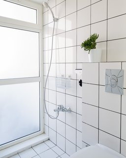 Large white tiles are repeated in the bathroom, which sits at the rear of the flat. A translucent window illuminates the space with natural light.
