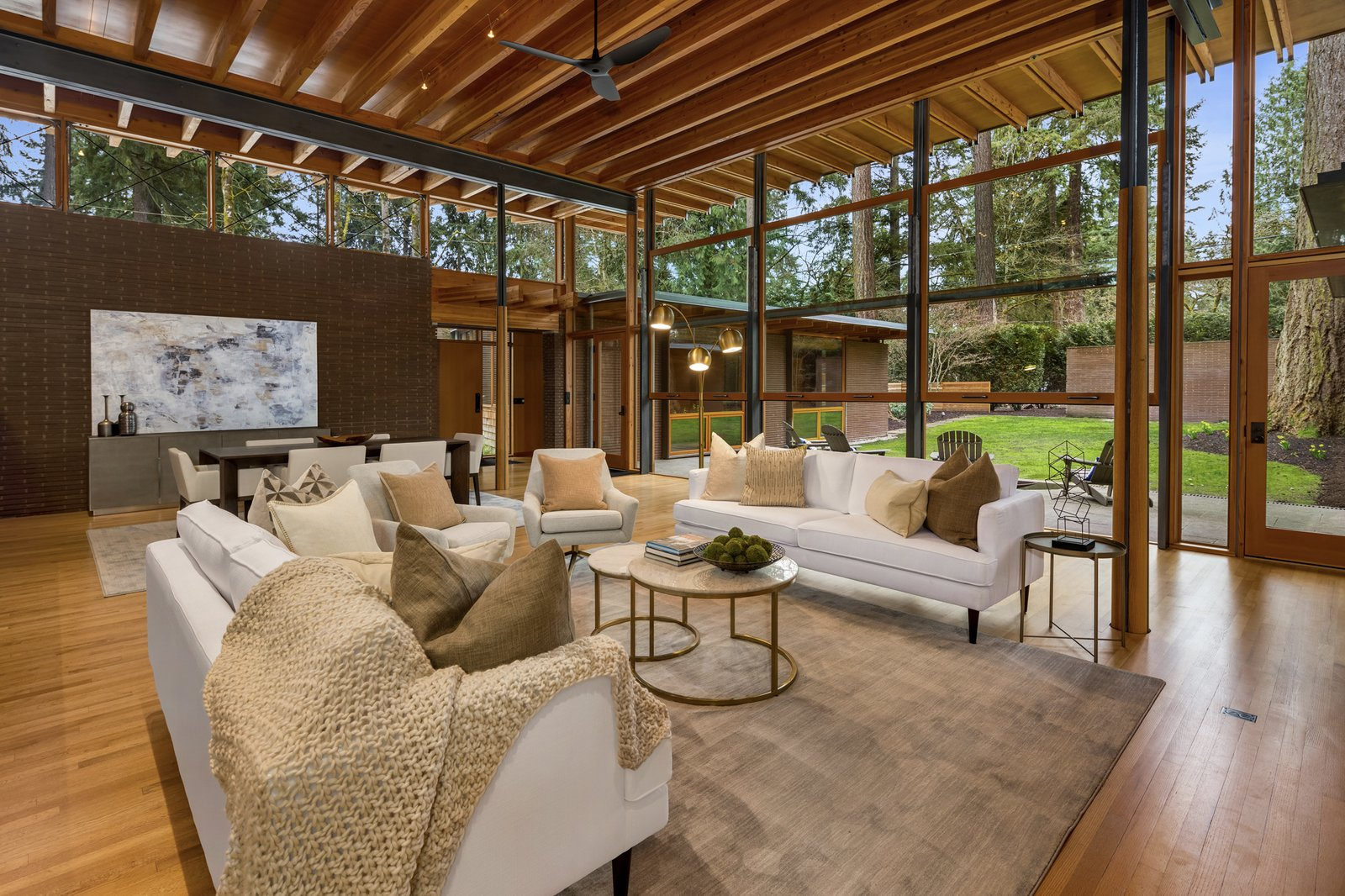 """Living Room, Sofa, Ceiling Lighting, End Tables, Chair, Track Lighting, Medium Hardwood Floor, and Coffee Tables Built in 2014, this contemporary home is located in Beaux Arts Village, <span style=""""font-family: Theinhardt, -apple-system, BlinkMacSystemFont, &quot;Segoe UI&quot;, Roboto, Oxygen-Sans, Ubuntu, Cantarell, &quot;Helvetica Neue&quot;, sans-serif;"""">a small, lakeside town across the water from Seattle, Washington, near Bellevue. The single-story home is comprised of two wings, with a double-height central great room overlooking </span>  Photo 1 of 7 in A Jim Cutler–Designed Beaux Arts Contemporary Asks $5.2M"""