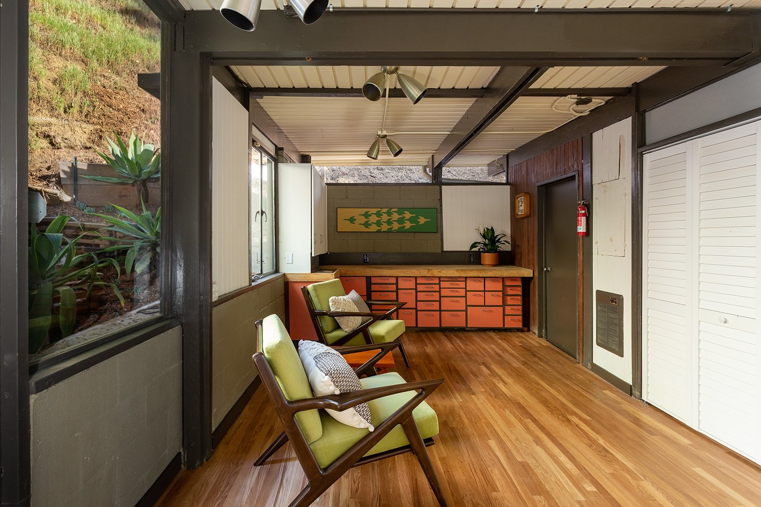 A large entertaining or craft area offers a large work are with built-in cabinetry at one end.  Photo 15 of 17 in A Dapper Midcentury Under the Hollywood Sign Lists for $1.65M