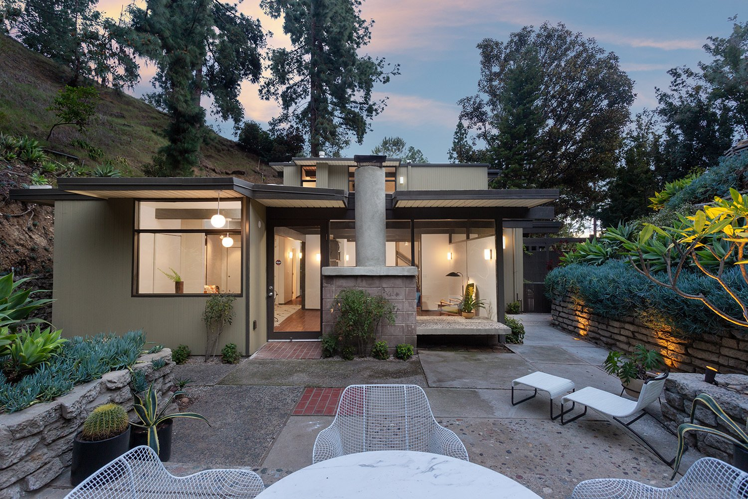 The side of the home opens onto a lush patio, complete with terraced planters and new landscape lighting. Views from the opposite direction look up to the Hollywood sign.  Photo 16 of 17 in A Dapper Midcentury Under the Hollywood Sign Lists for $1.65M