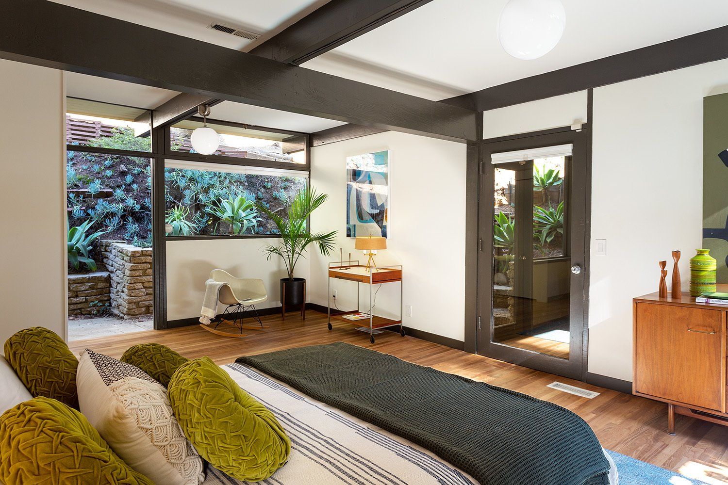 Red brick is traded for hardwood floors in all of the home's bedrooms. Here, the master bedroom provides direct access to the backyard.  Photo 11 of 17 in A Dapper Midcentury Under the Hollywood Sign Lists for $1.65M