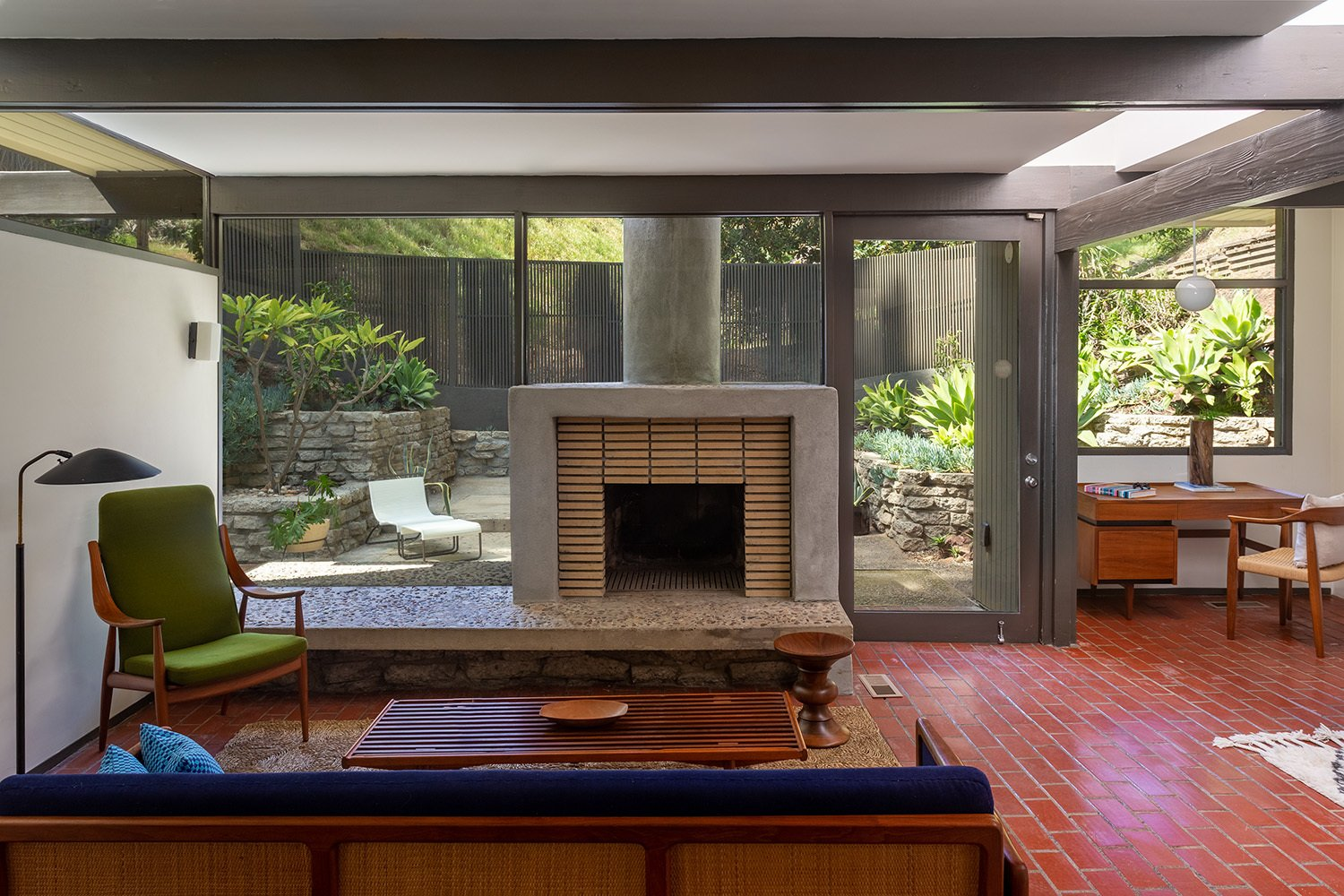 A concrete and brick fireplace anchors the main living area, which also connects to a small office area. Glass walls overlook a large patio surrounding the home.  Photo 5 of 17 in A Dapper Midcentury Under the Hollywood Sign Lists for $1.65M