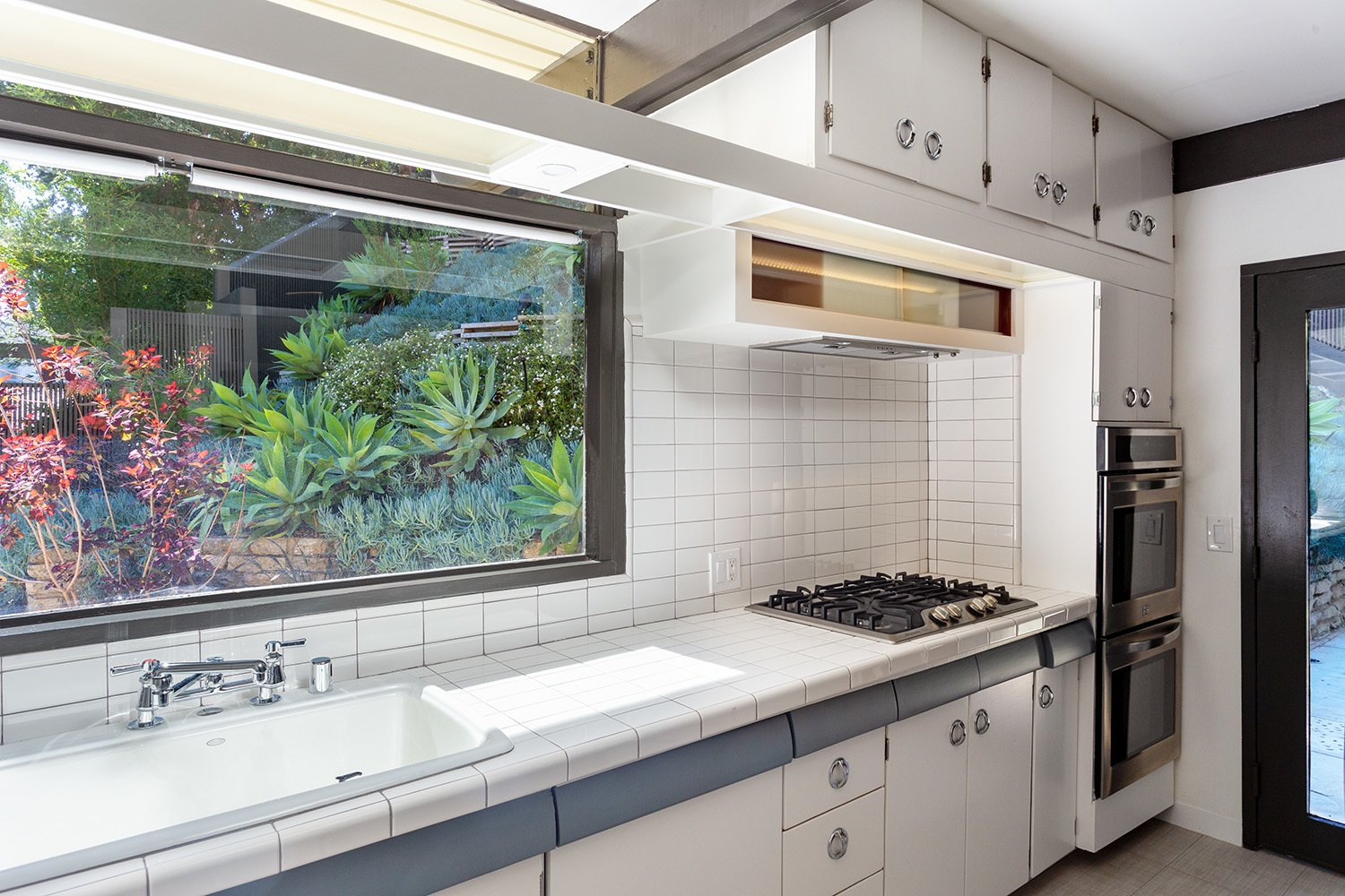 The kitchen features original cabinetry with a large window above the sink providing natural light. The space was updated with new appliances and fixtures.  Photo 9 of 17 in A Dapper Midcentury Under the Hollywood Sign Lists for $1.65M