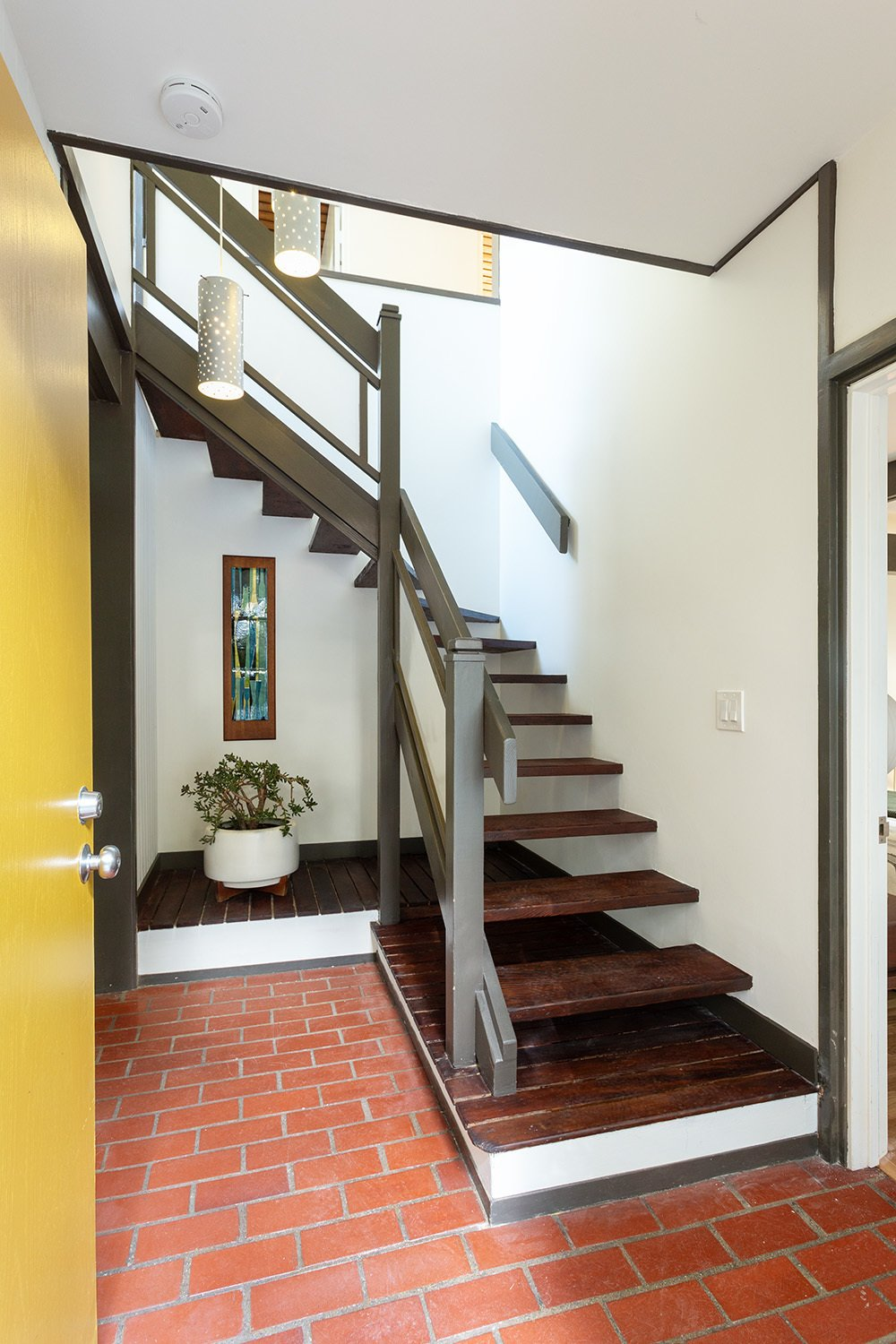 Malinoff designed the home while training to become an architect at the University of Southern California School of Architecture. The recently renovated interior showcases many original details, including red brick floors, simple wooden details, and a midcentury color palette.  Photo 3 of 17 in A Dapper Midcentury Under the Hollywood Sign Lists for $1.65M