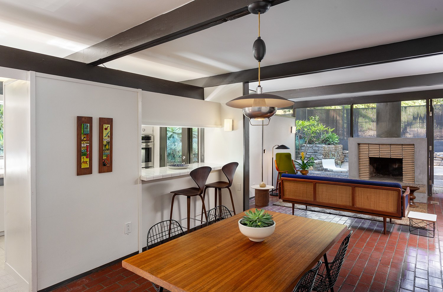 The foyer opens up into the dining and living area. Painted beams and trim highlight the structure's post-and-beam design.  Photo 4 of 17 in A Dapper Midcentury Under the Hollywood Sign Lists for $1.65M