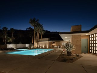 At night, recessed lights trace the structure along the overhang while the pool glows in the moonlight.