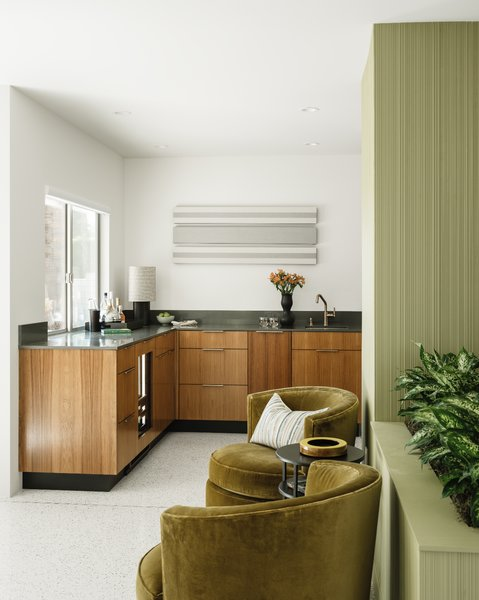 The light-filled, corner wet bar complements the kitchen design with custom teak cabinets.