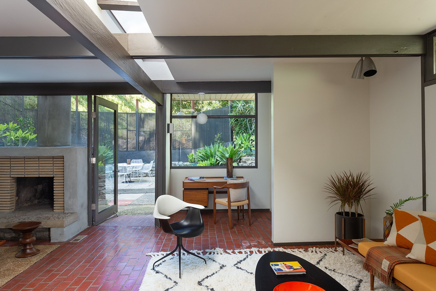 A closer look at the office area and an additional seating nook. A narrow band of skylights cast sunlight into space.  Photo 6 of 17 in A Dapper Midcentury Under the Hollywood Sign Lists for $1.65M