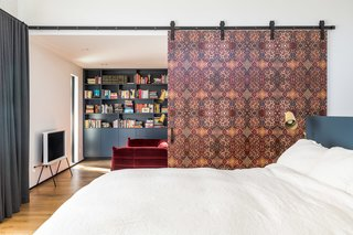 A colorful sliding wall provides privacy and a pop of colorful pattern in the master bedroom.