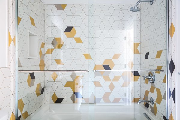 The shower is clad with a playful, abstract array of white, gold, and black tiles.