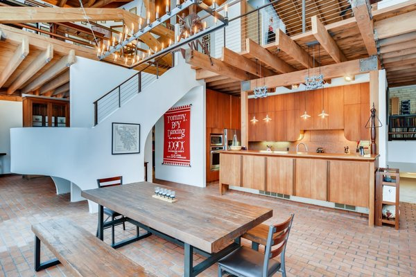 The double-height space features expansive public areas along the ground floor, with original brick and wood details throughout. A dining area is open to the kitchen in the corner while a staircase curves around while leading to a catwalk upstairs.