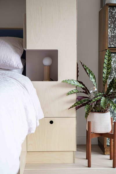 Small niches on both sides of the Murphy bed function as bedside tables. Drawers and cabinets of various sizes offer storage on both sides of the bed.