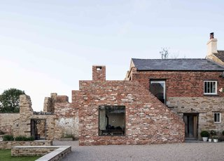 The disorderly nature of the ruin is juxtaposed against the modern extension and Victorian-era residence. The facade brickwork was largely completed using reclaimed materials, allowing the new section to sensitively blend into its surroundings.