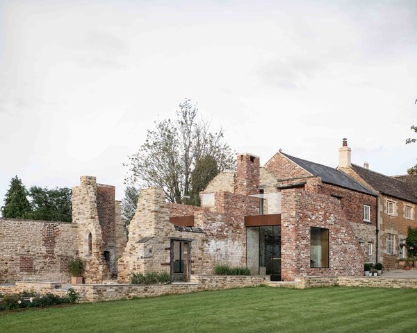 Located about an hour northwest of London in Northamptonshire, a Grade II listed Victorian home was extended to encompass an adjacent cattle barn and historic ruin.