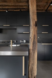 An original timber post stands beside the new sleek cabinetry and stainless-steel countertops.