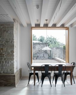 The new dining area looks out onto the front garden. Will Gamble Architects designed a concrete plinth to run along the base of the stone walls as a monolithic 'skirting' design.