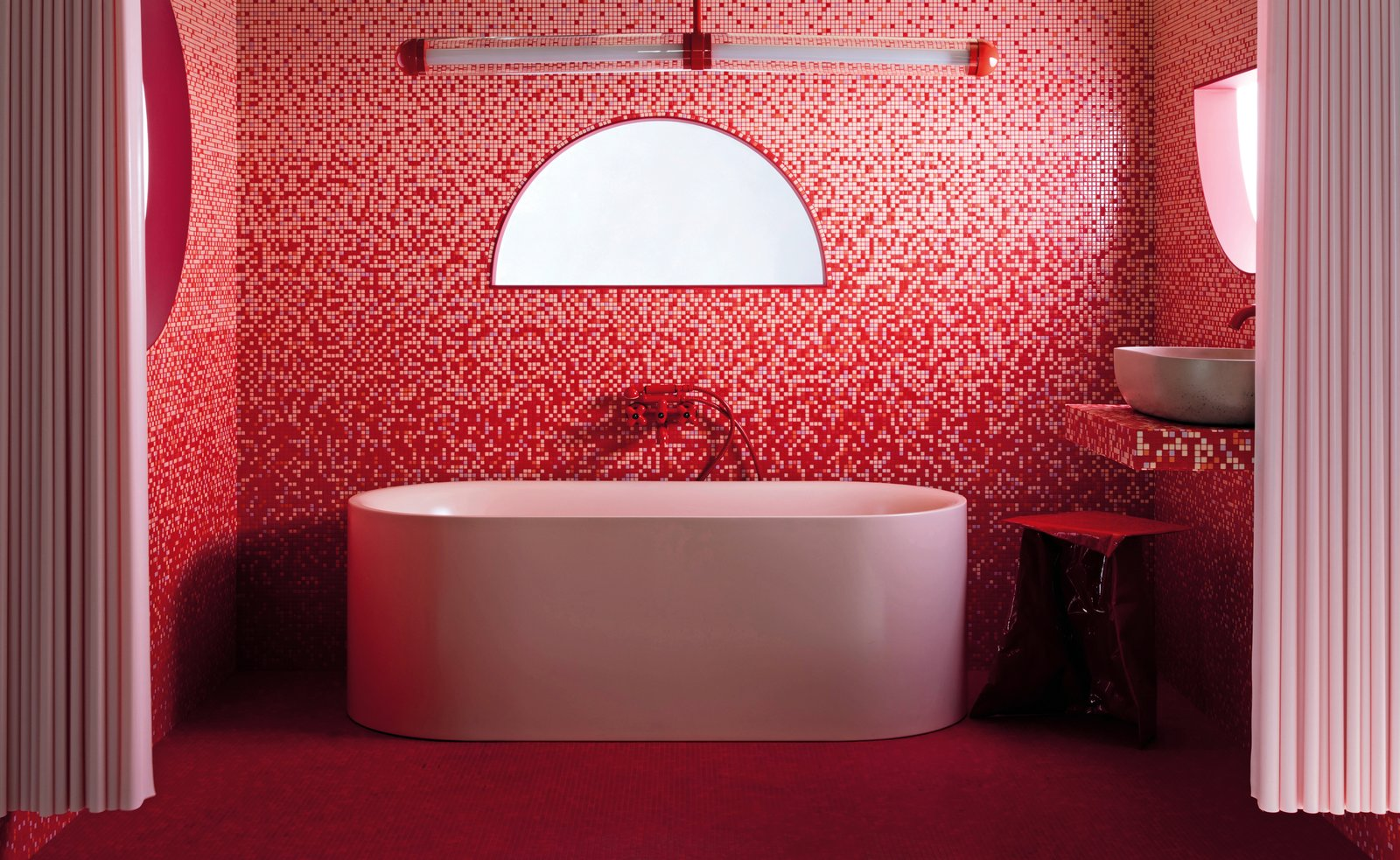 """Bath, Tile, Freestanding, Mosaic Tile, Pendant, and Vessel Bespoke mosaic tiles in several shades of matte and gloss pink, along with red Bisazza tiles, create a dramatic ombre effect in this bathroom. The light above the bath is a special-edition, red version of the 2LG Studio Capsule collection designed in collaboration with Cameron Design House, who noted that """"pink and red aren't a traditional color combination, but they work really well here.""""  Bath Mosaic Tile Tile Photos from Put Lipstick on Your Door: 5 Ways to Make Your Home Unapologetically Bold"""