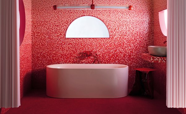 "Bespoke mosaic tiles in several shades of matte and gloss pink, along with red Bisazza tiles, create a dramatic ombre effect in this bathroom. The light above the bath is a special-edition, red version of the 2LG Studio Capsule collection designed in collaboration with Cameron Design House, who noted that ""pink and red aren't a traditional color combination, but they work really well here."""