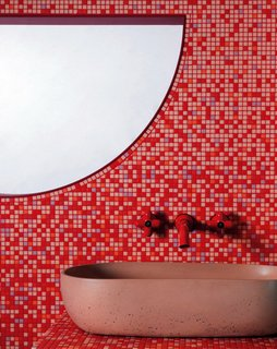 """This bathroom was inspired by '70s cult horror film Suspiria by Dario Argento,"" says Cluroe. ""Film is always an influence on our work, and the use of color in that film is so dramatic in quite a camp way. We wanted to tap into that and see if we could go there."" The pink sink is by Kast, and the retro red taps are by Fantini."