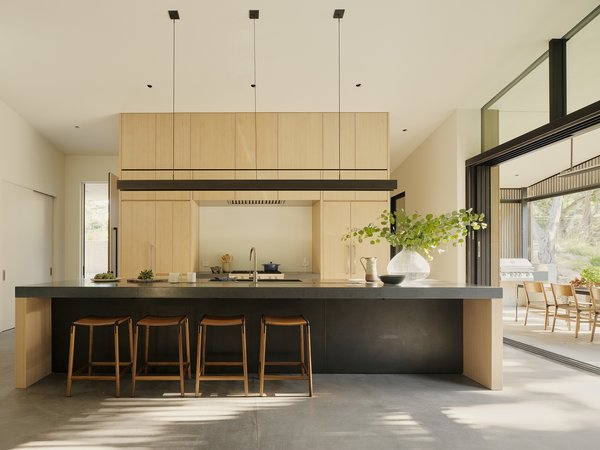 "Large sliders by LaCantina Doors bring ample light into the kitchen, which features a blackened steel pendant by the architects and De Haro counter stools by Fyrn. <span style=""font-family: Theinhardt, -apple-system, BlinkMacSystemFont, &quot;Segoe UI&quot;, Roboto, Oxygen-Sans, Ubuntu, Cantarell, &quot;Helvetica Neue&quot;, sans-serif;"">Concreteworks countertops, a Wolf range, Kallista sink, and Boffi faucet also fill the space.</span>"