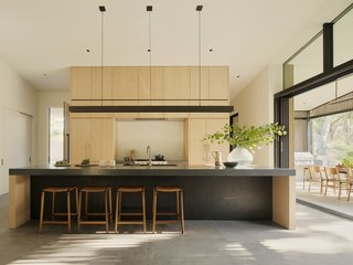 """Large sliders by LaCantina Doors bring ample light into the kitchen, which features a blackened steel pendant by the architects and De Haro counter stools by Fyrn. <span style=""""font-family: Theinhardt, -apple-system, BlinkMacSystemFont, &quot;Segoe UI&quot;, Roboto, Oxygen-Sans, Ubuntu, Cantarell, &quot;Helvetica Neue&quot;, sans-serif;"""">Concreteworks countertops, a Wolf range, Kallista sink, and Boffi faucet also fill the space.</span>"""