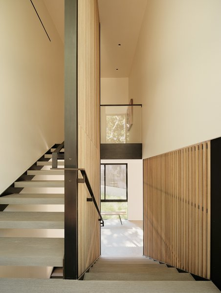 The architects used cedar slats to enclose a steel-and-concrete staircase that leads to the master bedroom upstairs.