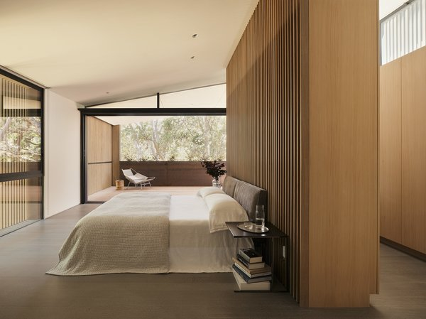 In the master bedroom, Leger bedside tables by Rodolfo Dordoni for Minotti sit alongside a Lifesteel bed by Antonio Citterio for Flexform in the master bedroom. The linens are by Coyuchi. Glass sliders lead to a large deck.