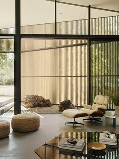 A large slider opens onto a small courtyard and the outdoors. The lounge chairs and ottoman are by Charles and Ray Eames for Herman Miller and the Rivet side table is from Frama.
