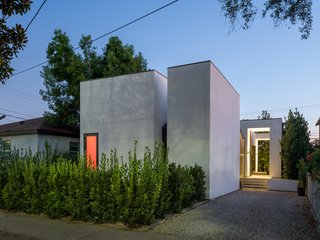 A nighttime view reveals the glow of the pink interior and the entrance open to the backyard.