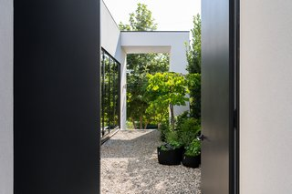 The black front door opens to reveal a courtyard that leads to down to the backyard pool. With an eye to sustainability, the couple replaced the existing concrete with gravel.