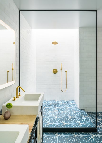 In the skylit master bathroom, Dandelion tile from Marrakech Design is paired with tile from Ann Sacks. The fixtures are by California Faucets and the mirror is from Paris Mirrors.