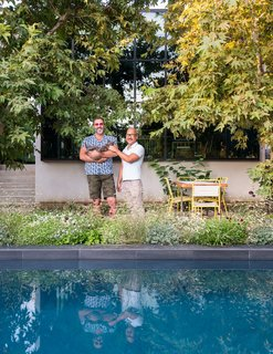 Guy (holding Pickles the cat) and Mark transformed the backyard, adding a pool and planting sycamore trees and native grasses. A custom dining table by Angel City Lumber is paired with vintage chairs from Amsterdam Modern.