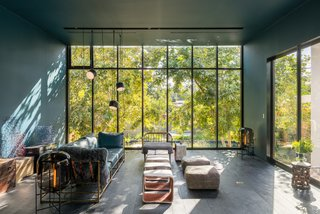 A sofa by Stephen Kenn Studio joins ceramic tables by artist Ben Medansky in the glass-walled living area. The AIM pendants are by Ronan and Erwan Bouroullec for Flos and the Oda floor lamps are from Pulpo. The metal artworks are by Guy.