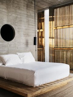 In the house's single bedroom, a queen-size bed sits on a platform constructed by local woodworkers.