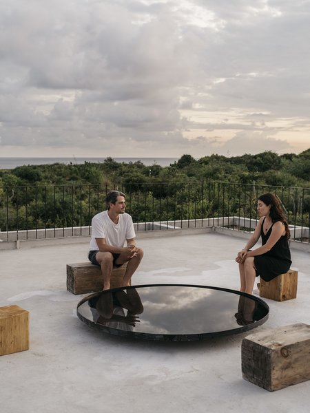 "On the roof, Claudio and Aranza sit on salvaged blocks of wood around a ""water mirror"" that reflects the sky. On clear nights, you can gaze both up and down at the stars, an activity that gives Casa Cosmos its name."