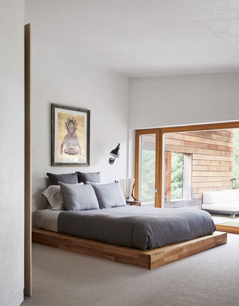 "The master bedroom in this prefab passive house in the Catskills looks out onto a private, cantilevered deck. ""This house for me is about contemplation,"" says homeowner Adrian. ""You come here from the city and the place is saying, 'Hi, meet yourself again.'"" A low platform bed with stacked pillows instead of a headboard helps maintain that casual feel."