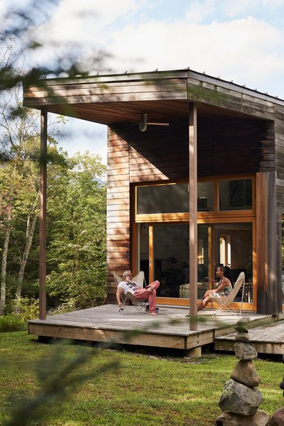 Adrian Bueno and Yvette Leeper-Bueno sit on the simple platform porch that extends from the living room of their weekend retreat in Saugerties, New York.